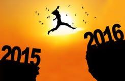 Frau springen durch Abstand mit Zahlen 2015 und 2016 Lizenzfreie Stockfotografie