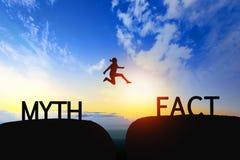 Frau springen durch den Abstand zwischen Mythos zur Tatsache auf Sonnenuntergang lizenzfreie stockfotos