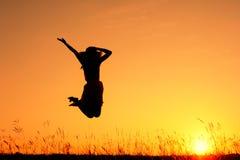 Frau springen und Sonnenuntergangschattenbild Stockfotografie