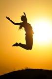Frau springen und Sonnenuntergangschattenbild Lizenzfreie Stockfotografie