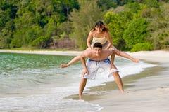 Frau springen von der Rückseite eines Kerls Lizenzfreies Stockfoto