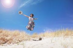 Frau springt auf den Strand Stockfotografie