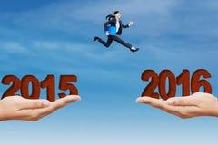 Frau springt auf die Klippe mit Zahlen 2015 und 2016 Stockfotografie