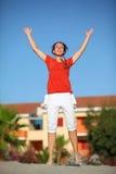 Frau springt auf Strand und hebt Hände zum Himmel an Lizenzfreie Stockbilder