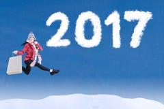 Frau springt mit 2017 auf Himmel Stockbild