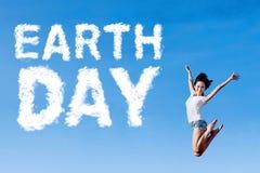 Frau springt mit Tag der Erde-Text Lizenzfreies Stockbild