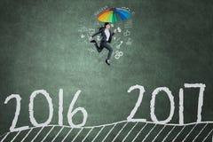 Frau springt in Richtung zu 2017 auf Tafel Stockfoto