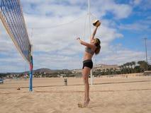 Frau springt und schlägt den Strandvolleyball Lizenzfreies Stockbild