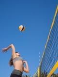 Frau springt und schlägt den Volleyball Lizenzfreie Stockfotografie