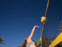 Frau springt und schlägt den Volleyball Stockbild