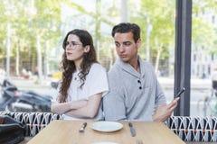 Frau störte zu ihrem Freund, der auf einem Restaurant sitzt lizenzfreie stockbilder
