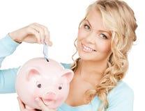 Frau steckt Bargeld in großes Sparschwein Stockbilder