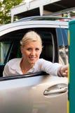 Frau steckt Parkenkarte in Sperre ein Stockbild