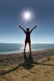 Frau steht auf Socken an Land gegenüber von Sonne Lizenzfreies Stockbild