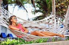 Frau steht in der Hängematte unter den Palmen auf dem tropischen still Lizenzfreies Stockfoto
