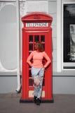 Frau steht in der Straße nahe bei einer roten Telefonzelle Lizenzfreies Stockfoto