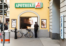 Frau steht an einer Wand und passt Poster für weibliche Haarpflege auf Lizenzfreie Stockfotos