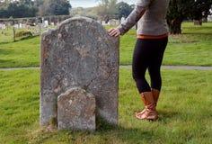Frau steht ihre Hand durchdacht auf einem Grundstein still stockfotografie