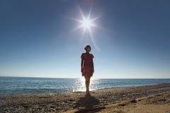 Frau steht an Land gegenüber von Sonne Lizenzfreie Stockfotografie