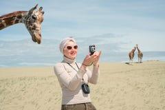 Frau steht nahe bei einer Giraffe und Fotografien stockfoto