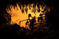 Frau steht nahe dem Eingang zu Lava Tube stockbild