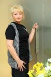 Frau steht nahe transparenter Tür Lizenzfreie Stockfotos
