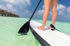 Frau steht oben Paddeleinstieg auf dem Ozean in Malediven lizenzfreies stockfoto