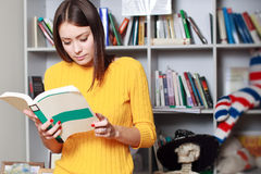 Frau steht Sofalesebuch still Lizenzfreie Stockfotos