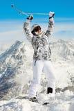 Frau steht, werfend oben Hände mit Skipolen Stockfotos