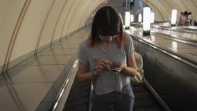 Frau steigen oben an der Rolltreppe von der Untertage-U-Bahn und von der Anwendung von Smartphone-Apps stock footage