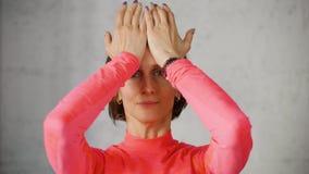 Frau stellt Hals gymnastische Pressen ihr Kopf gegen die Palmen ihrer Hände her stock footage