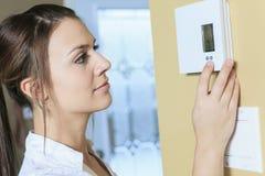 Frau stellte den Thermostat am Haus ein Stockbild