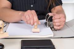 Frau stempelt ein Dokument mit einem Stempel Stockfotos