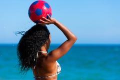 Frau am Strand, der Fußball spielt Lizenzfreie Stockfotografie