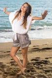 Frau am Strand, der seitlich ihre Arme verlängert Stockbild