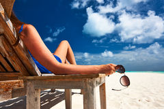 Frau am Strand, der Sonnenbrille hält Lizenzfreies Stockfoto