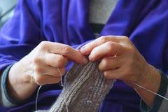 Frau strickt Schal der grauen Wolle mit Stricknadeln stockbilder