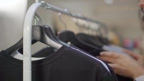 Frau sucht nach T-Shirt auf Gestell im Bekleidungsgeschäft, Nahaufnahme ihrer Hände stock video footage