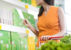 Frau am Supermarkt mit Einkaufsliste Stockbild
