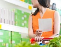 Frau am Supermarkt mit Einkaufsliste Stockbilder
