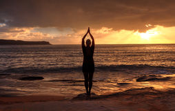 Frau Tadasana - Gebirgshaltungsyoga durch das Meer bei Sonnenaufgang Lizenzfreies Stockbild