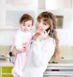 Frau am Telefon beim Halten ihres Babys in ihren Armen in der Ausrüstung Stockfotografie
