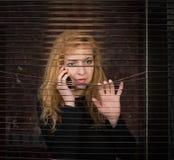 Frau am Telefon, das durch Jalousien schaut Lizenzfreies Stockbild