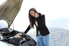 Frau am Telefon, das ein Zusammenbruchauto schaut Stockfotos