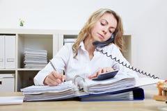 Frau am Telefon, das Kenntnisse nimmt Lizenzfreies Stockfoto