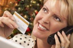 Frau am Telefon, das Kreditkarte nahe Weihnachtsbaum hält Stockfotos