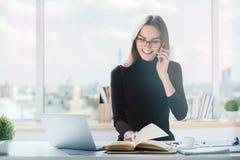 Frau am Telefon, das Schreibarbeit tut Lizenzfreie Stockfotos