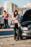 Frau am Telefon nach Autounfall Stockbild