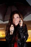 Frau am Telefon unter Regenschirm Stockfotos