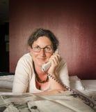 Frau am Telefon vor Zeitung auf Bett Lizenzfreie Stockbilder